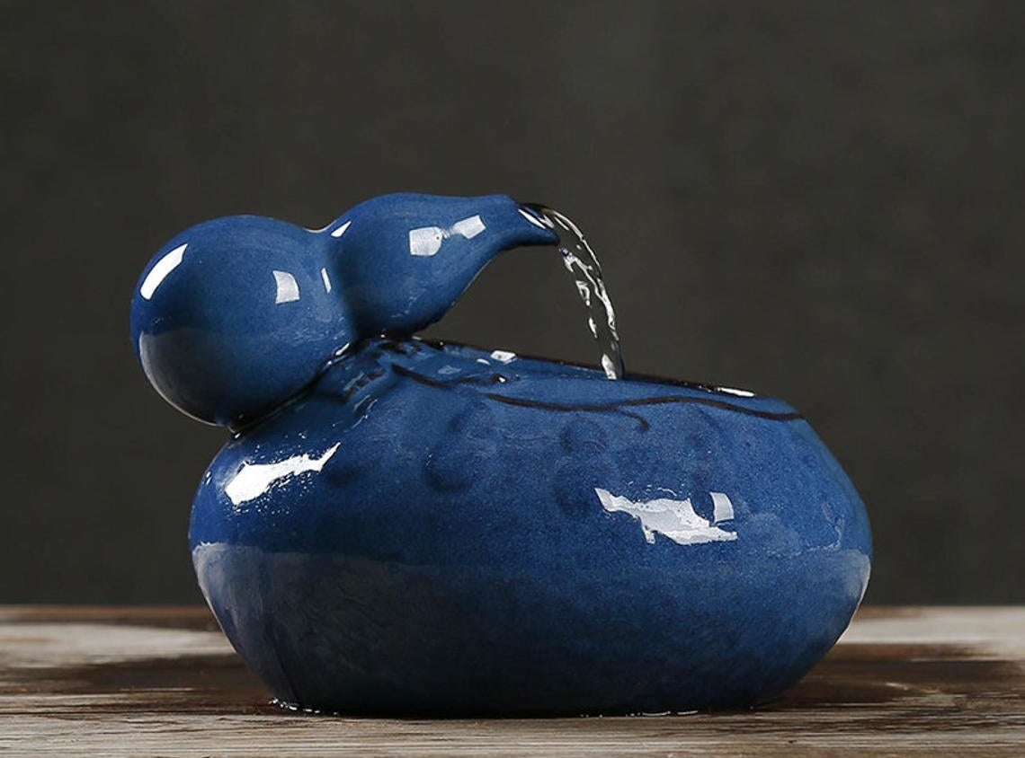 A close up of the ceramic cat bowl with water pouring through the spout