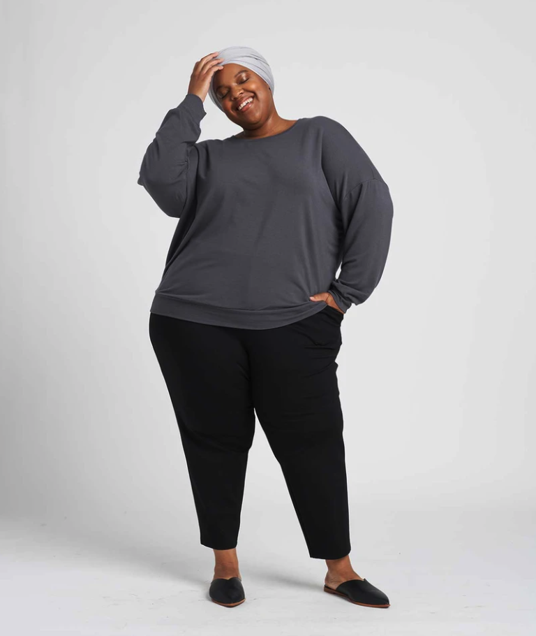 model wearing a gray sweatshirt and black pants
