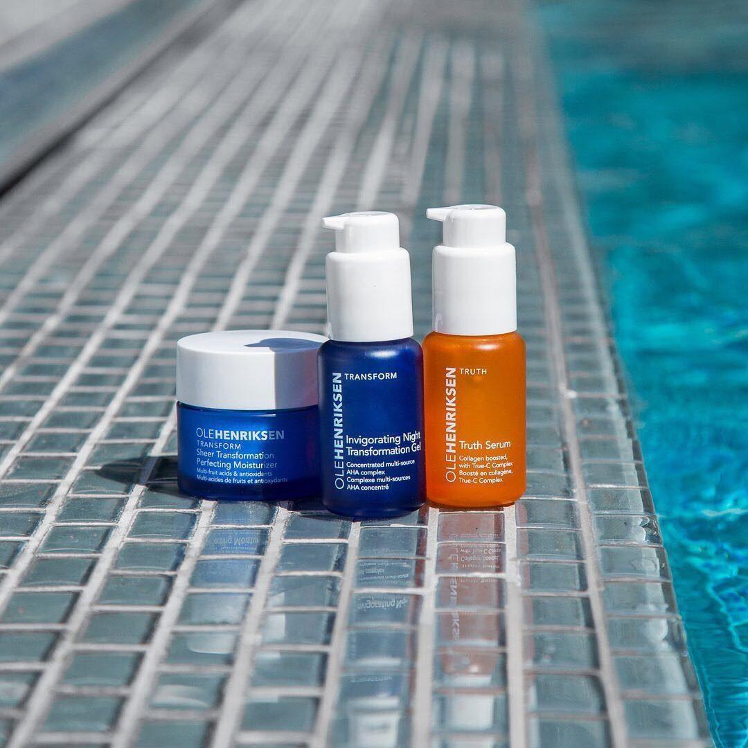 Ole Henriksen's serum, moisturizer, and night gel bottles pictured poolside
