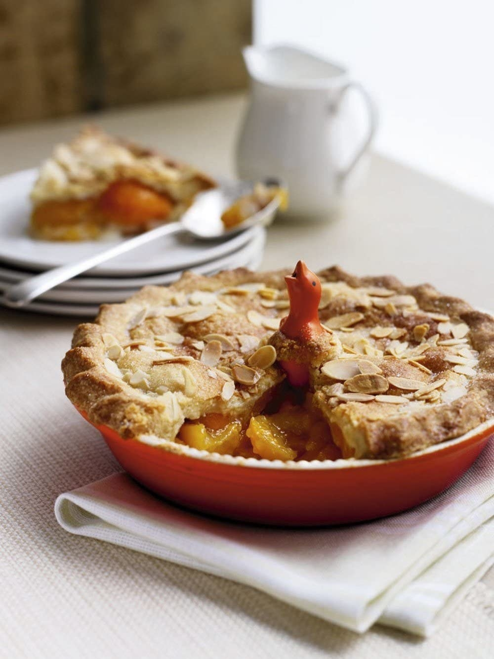 A peach pie with an orange pie bird baked into the middle