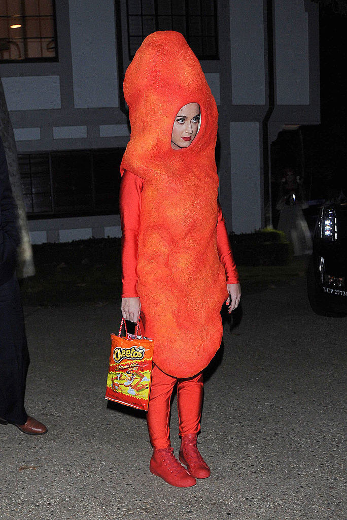 Katie Perry dressed as a Cheeto and holding a Cheeto bag purse for Halloween in 2014
