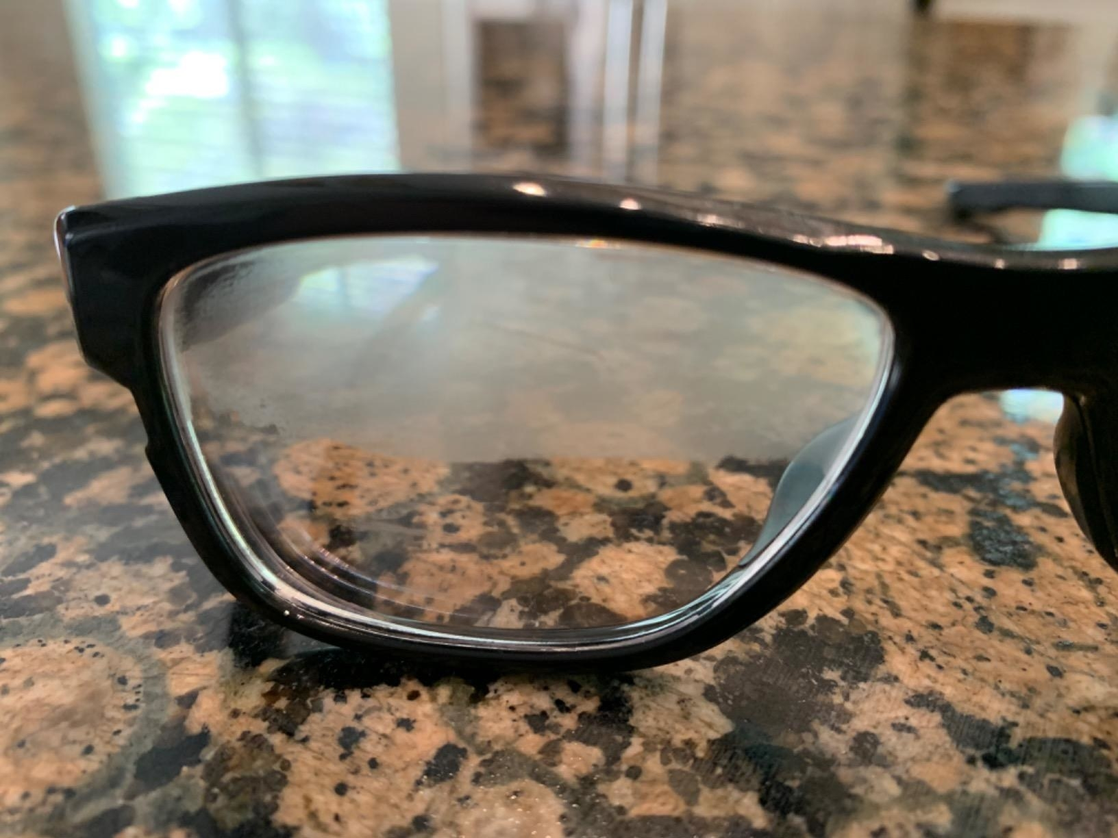 A glasses lens with fog on the top half and no fog on the bottom half