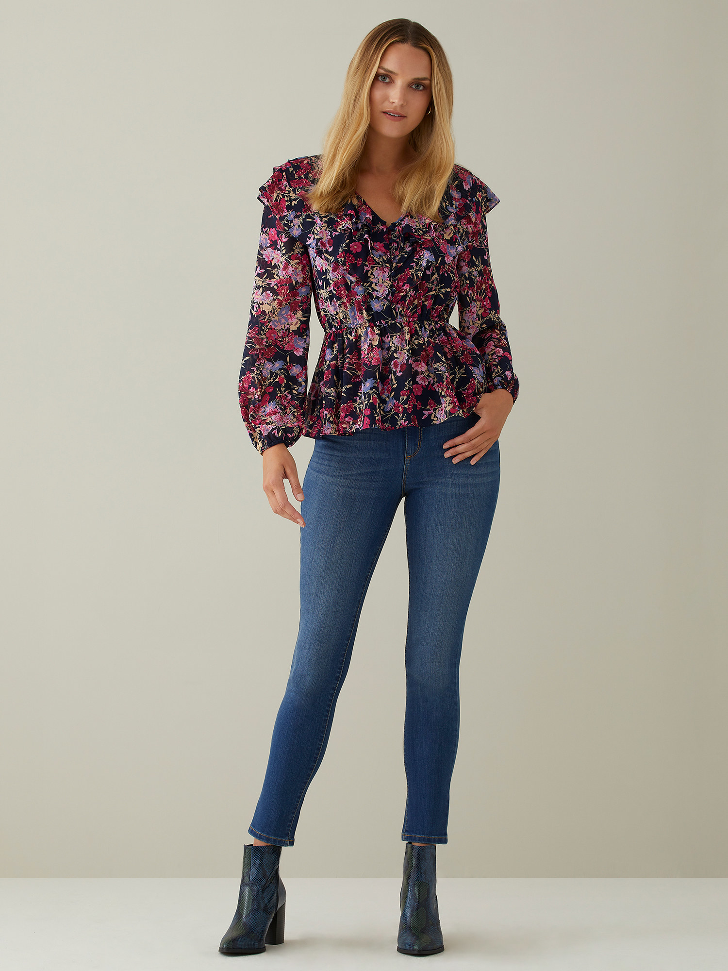Model wearing the pink and black ruffled blouse