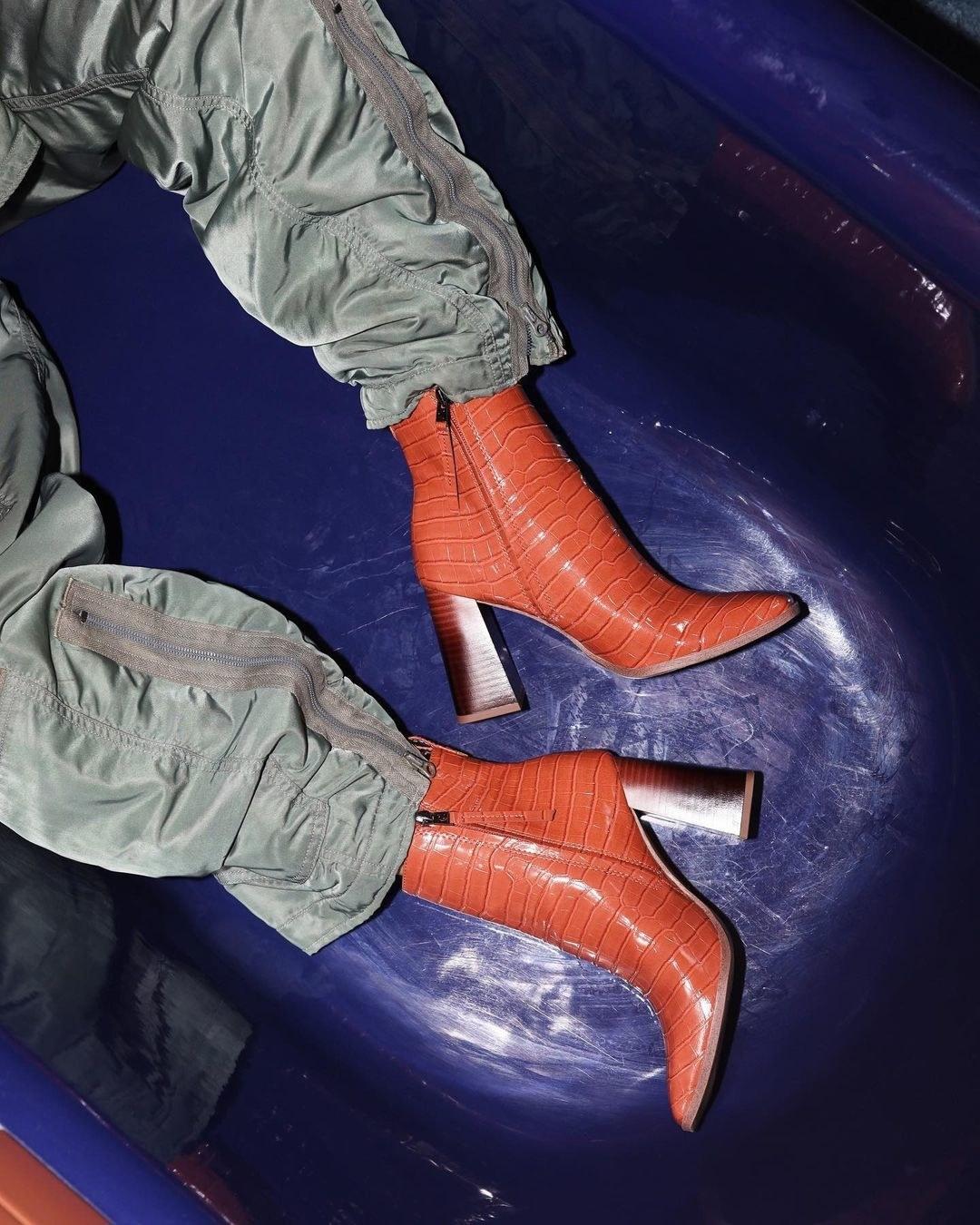 Model in the tan snakeskin booties with high wooden heels