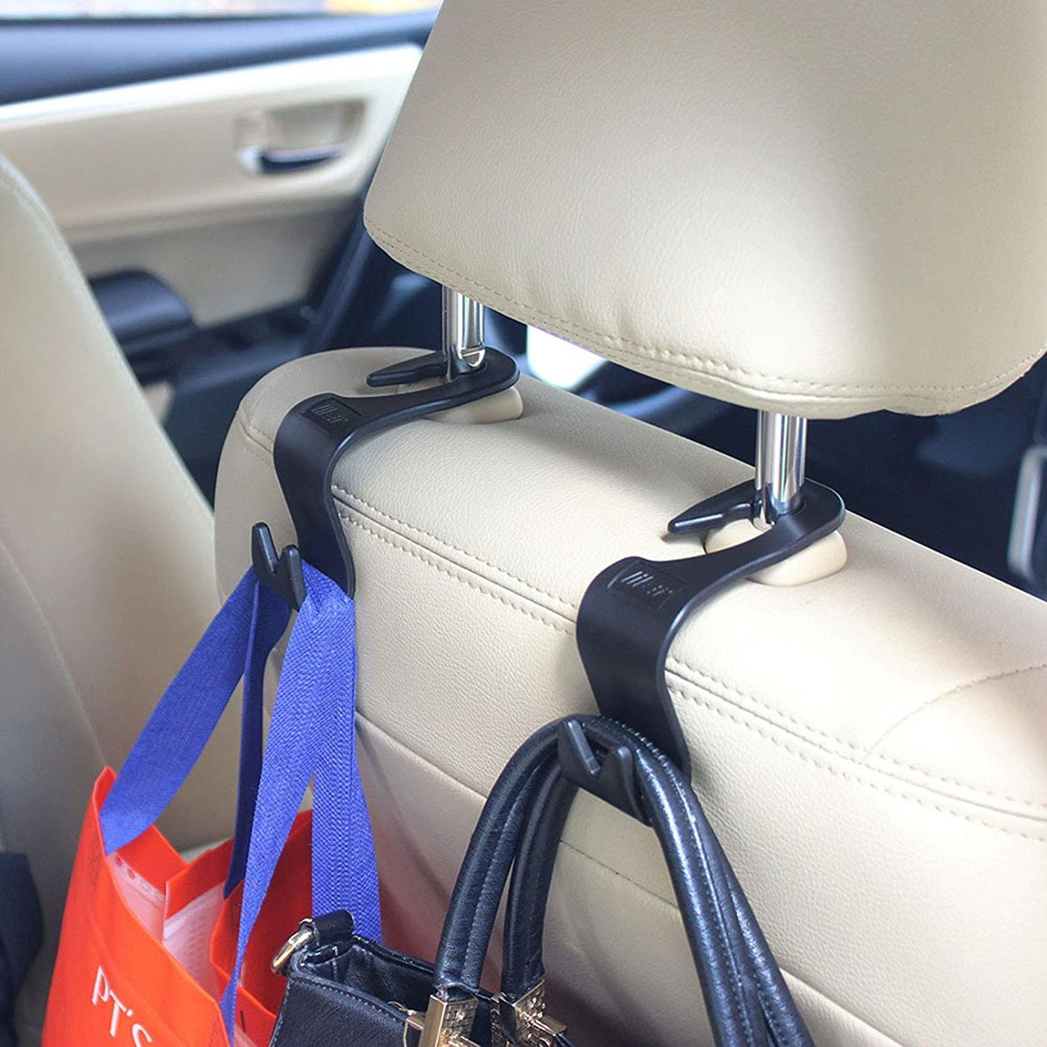 A purse and a bag hanging from hooks that are attached to a car head rest