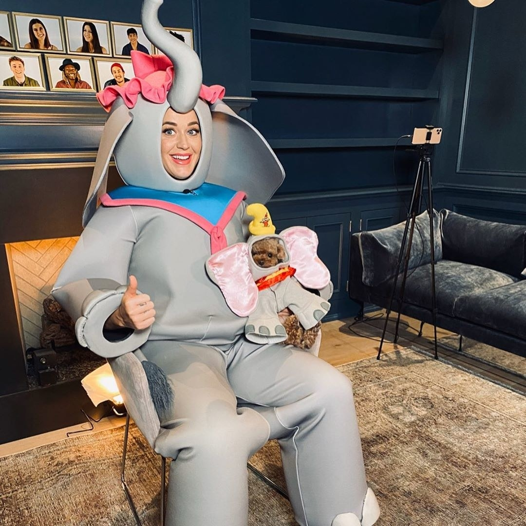 Katy posing with a dog dressed as Dumbo