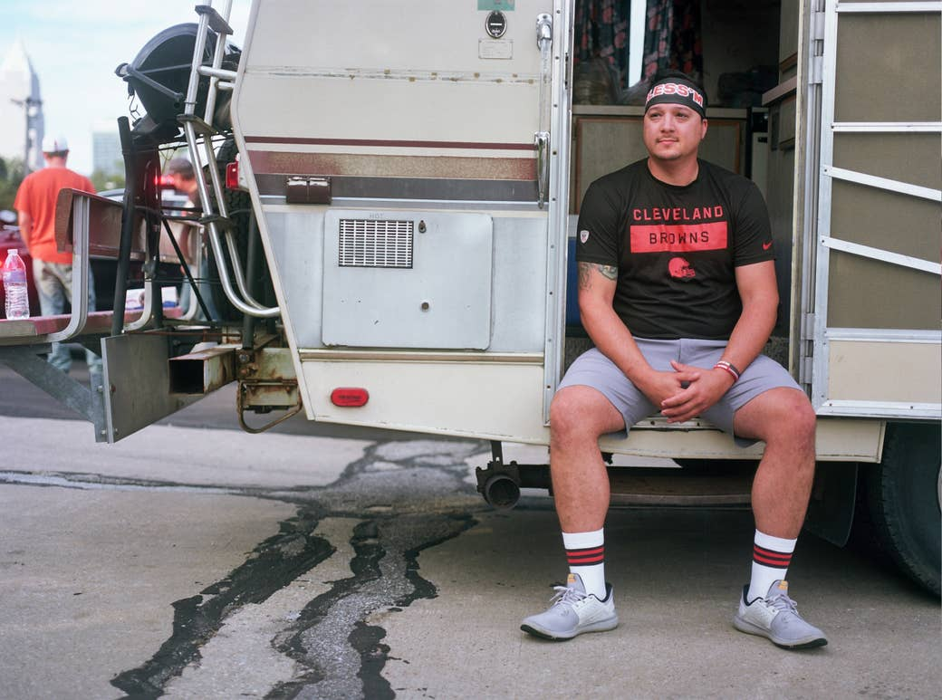 A man sits in a camper van with a Cleveland Browns T-shirt