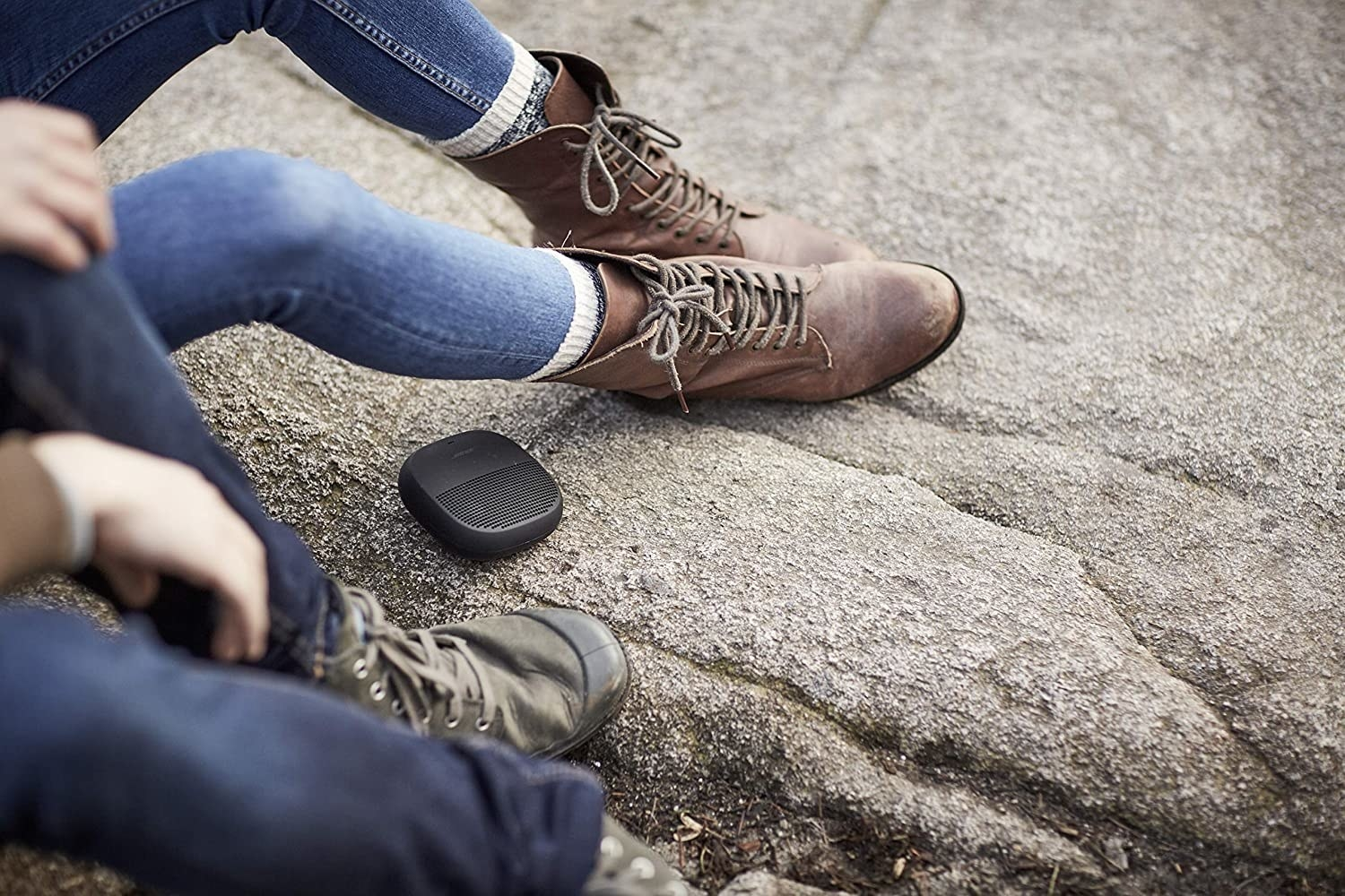The bose soundlink micro on rocky terrain with models sitting around it