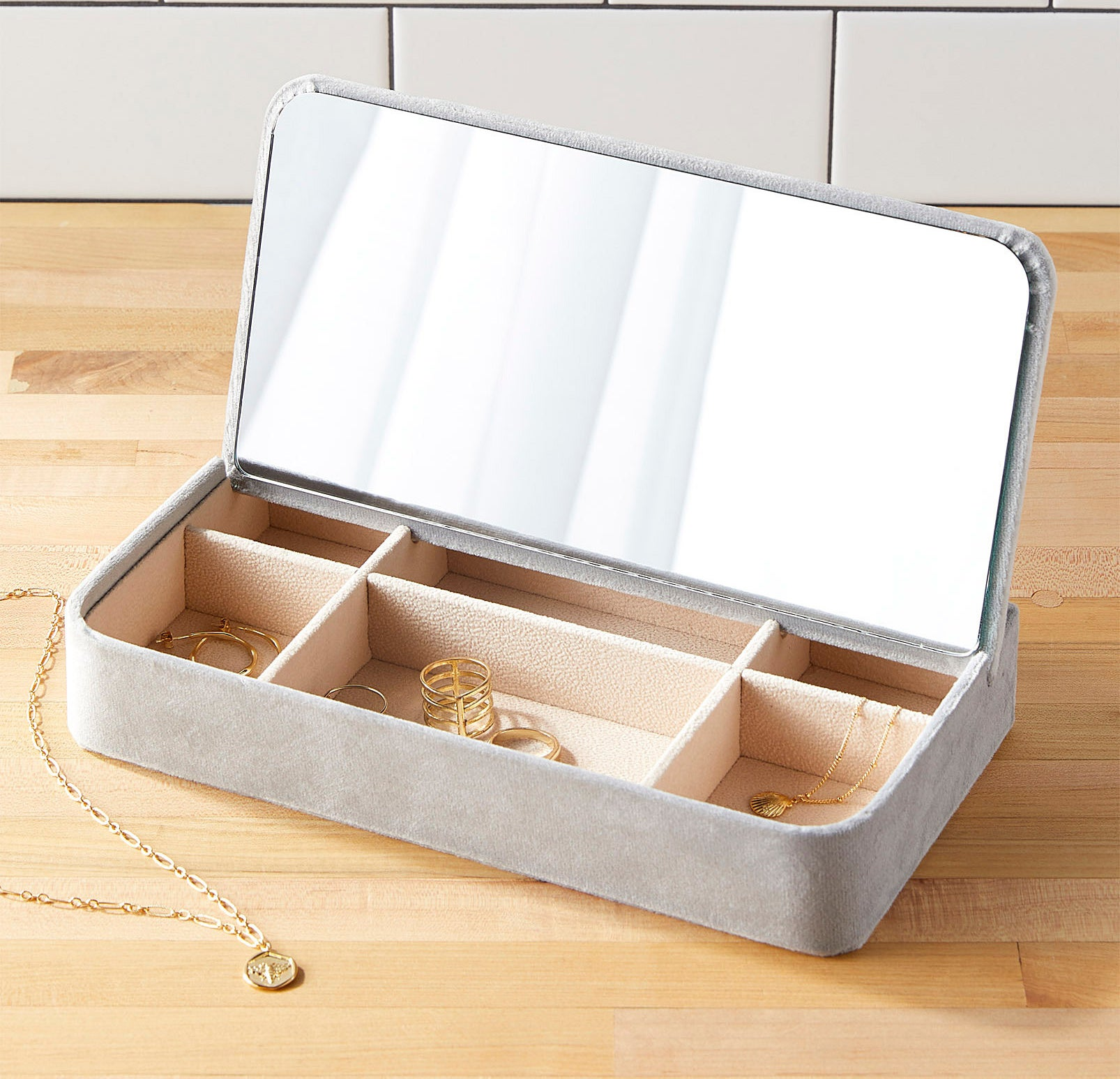 A velvet-covered jewelry box with a mirror and six little compartments filled with rings, earrings, and necklaces.