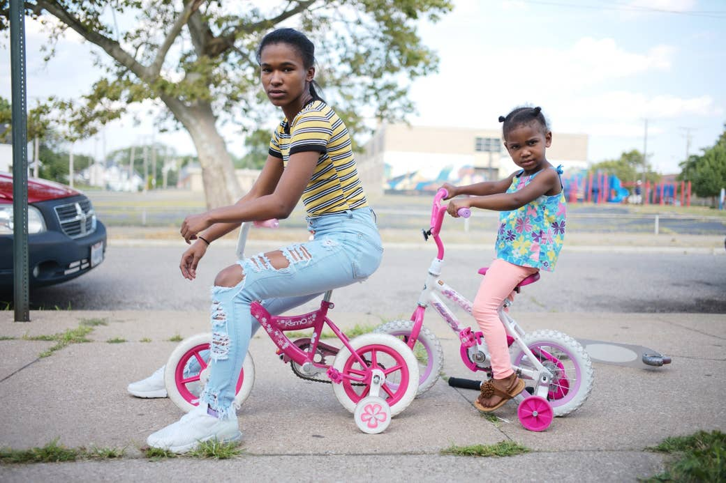 A woman and a child, both on children's bikes in the street