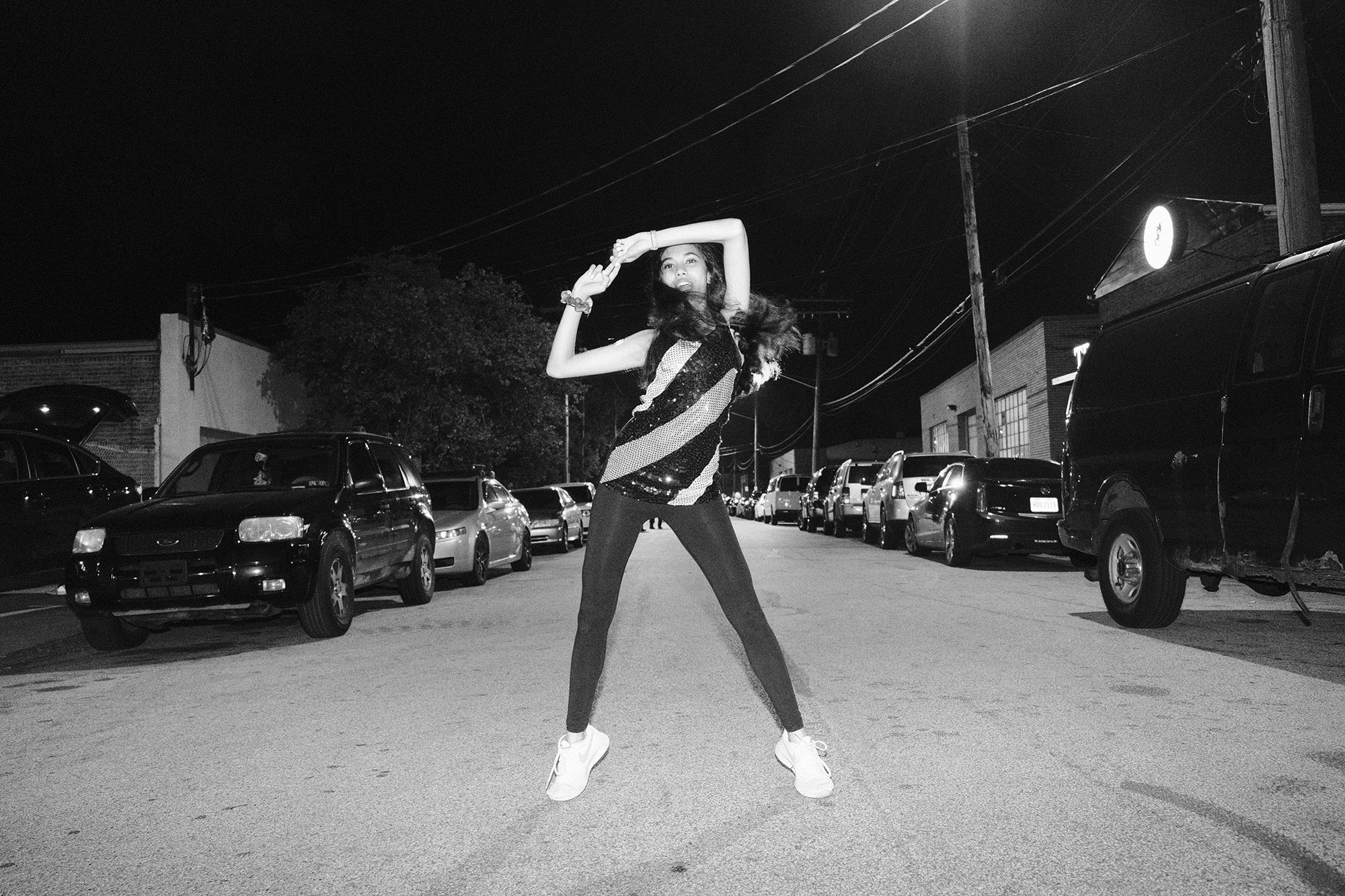 A black-and-white photo of a girl dancing in the street at night