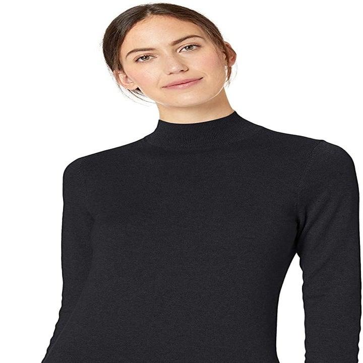 A model wearing a black mock neck sweater