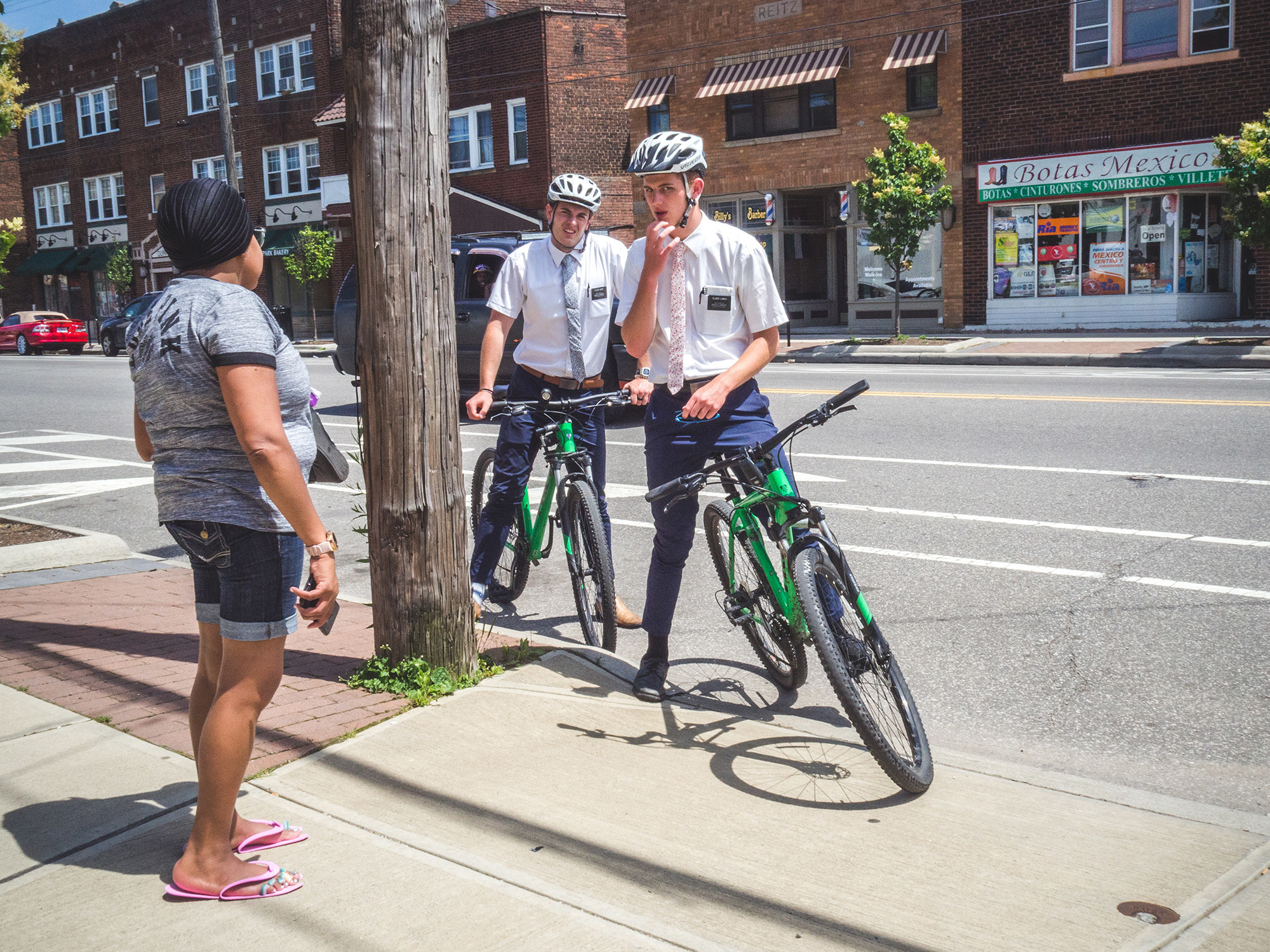 Two men in ties on bikes talk to a woman on the sidewalk