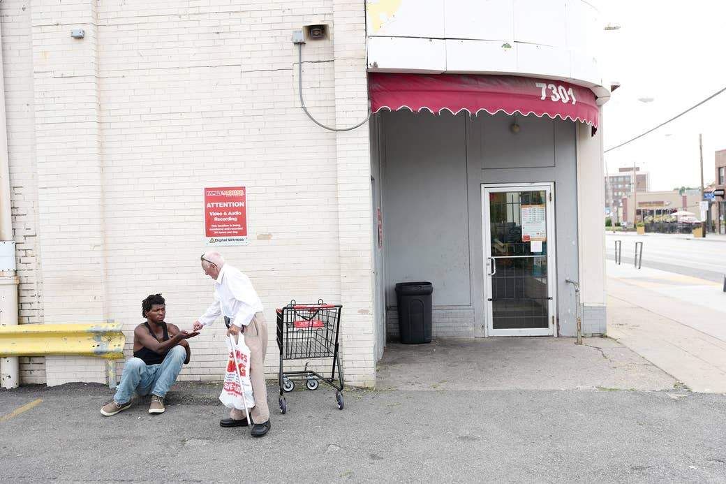 An older man leaving a store gives another man sitting on the ground money