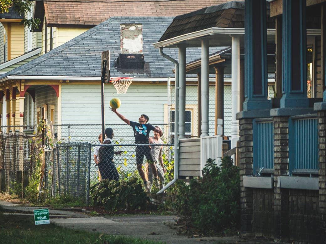 Boys playing basketball in a backyard