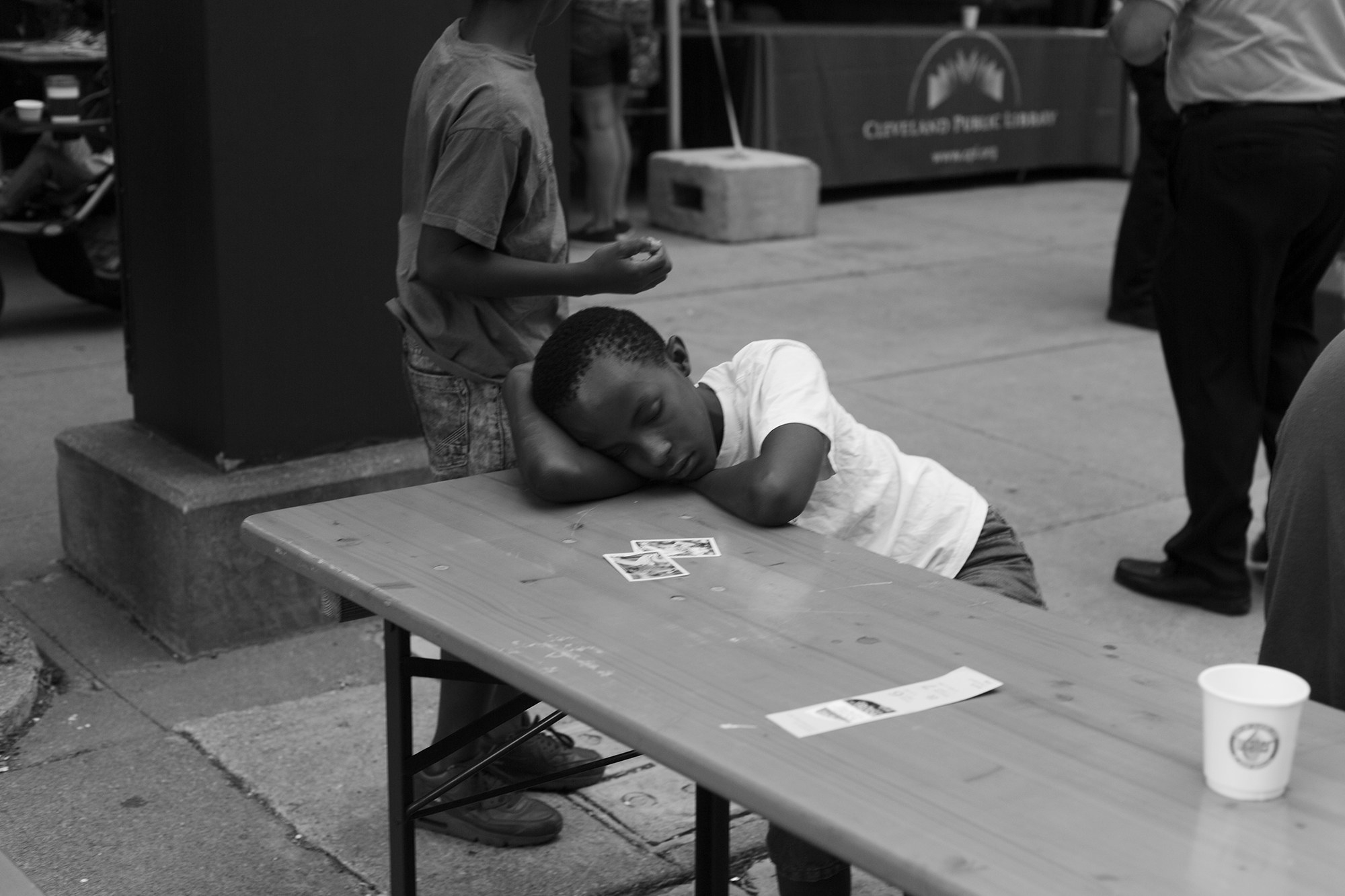 A small boy sleeps at a table outside while other children play in the background