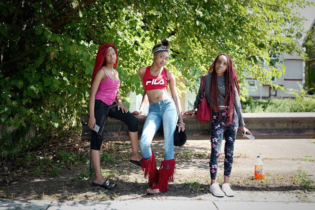Three women posing on a street median