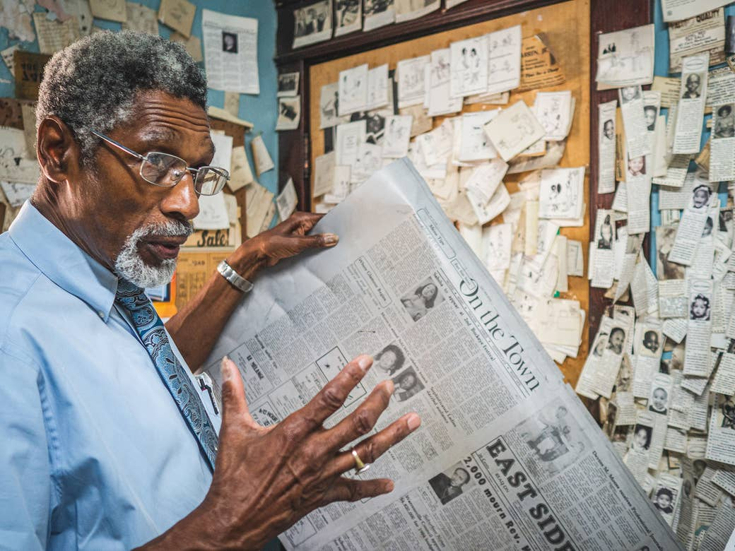 A man holds a newspaper in front of a wall filled with notes