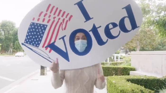 Katy Perry wearing a mask and a foam ''I voted'' sticker on her head