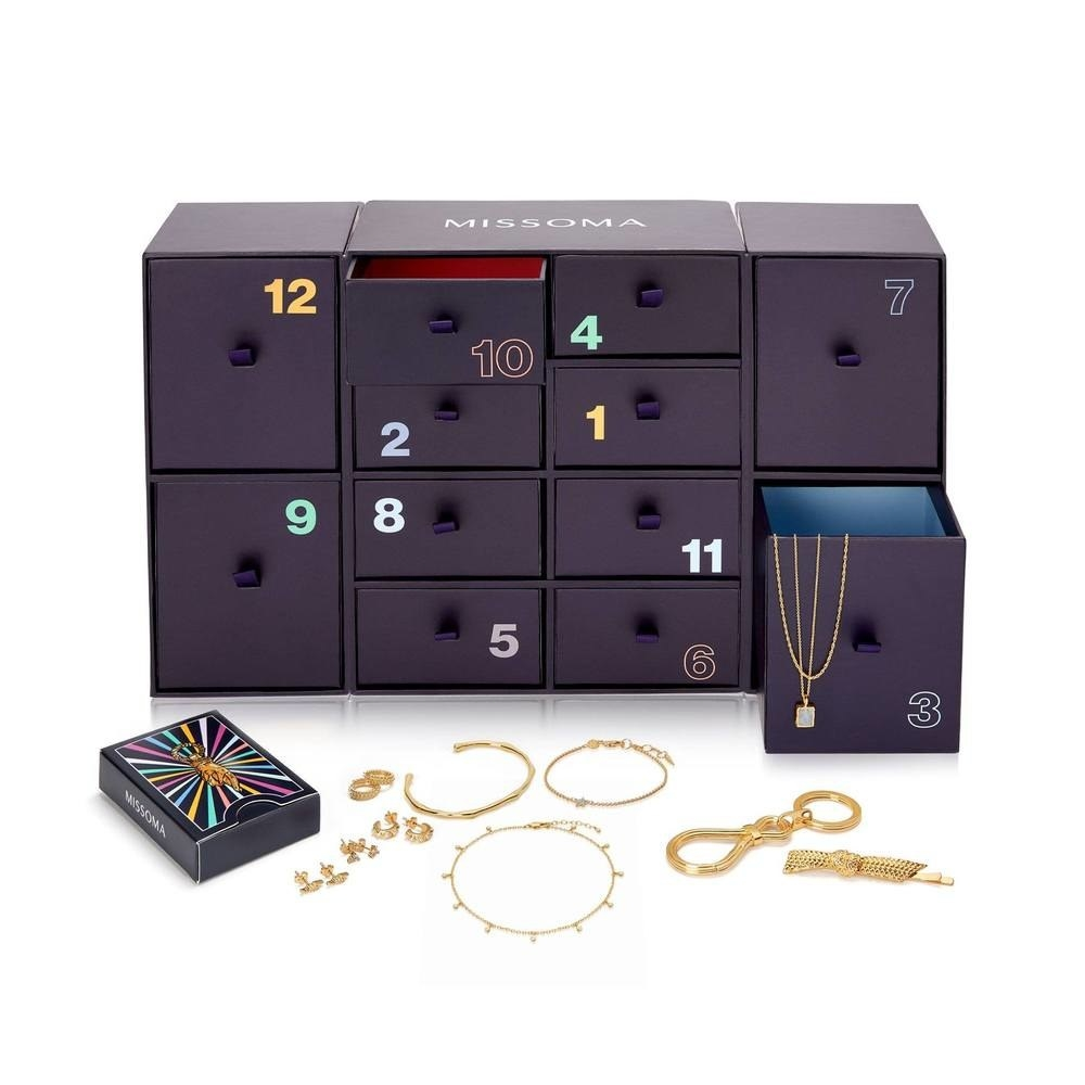 a purple set of drawers filled with gold layering jewelery