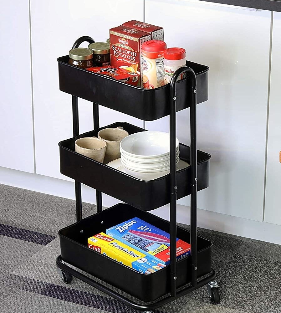 A metal rolling utility cart with spices in one shelf, plates and bowls on the second shelf, and plastic food wrap boxes on the lowest shelf