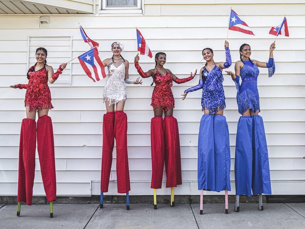 Five women on stilts holding Puerto Rican flags