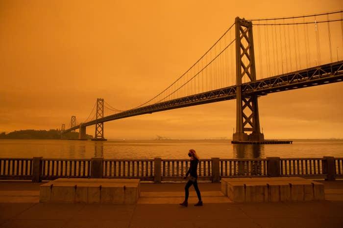 Woman wearing a mask walking past a bridge