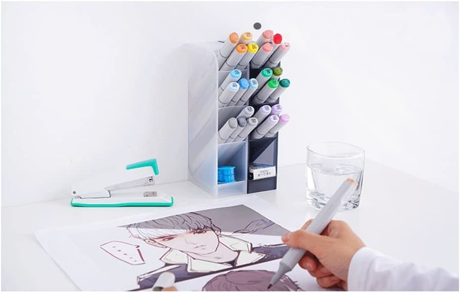 A person drawing at their desk with a small four tiered pencil holder in front of them