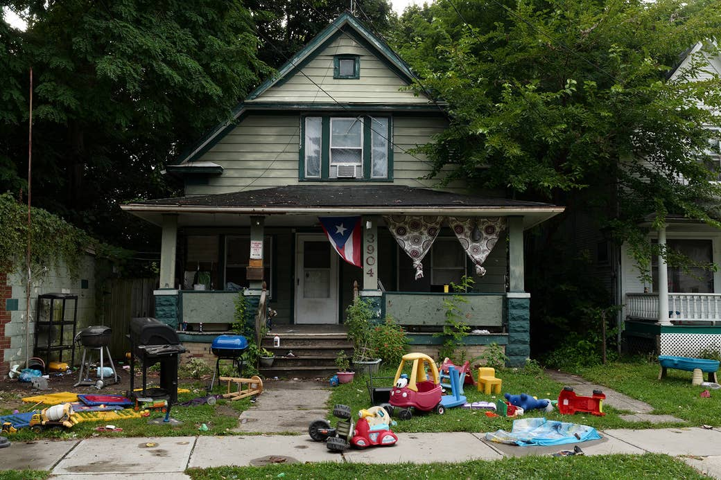 A house with lots of children's toys in the front yard