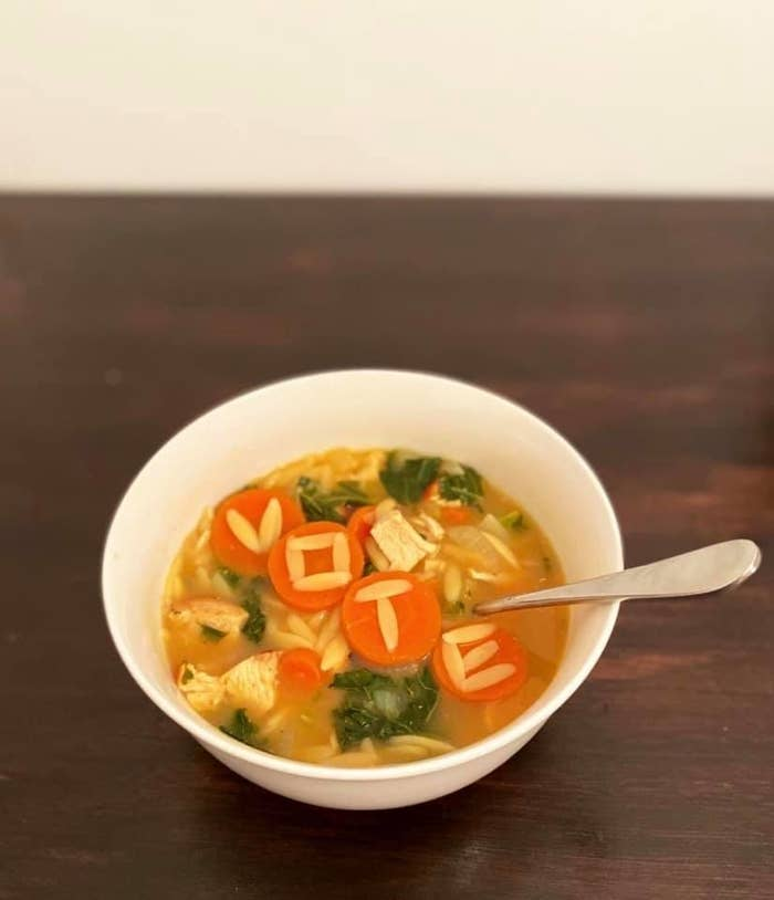"A bowl of chicken soup with ""vote"" spelled out in orzo pasta on top of sliced carrot rounds"