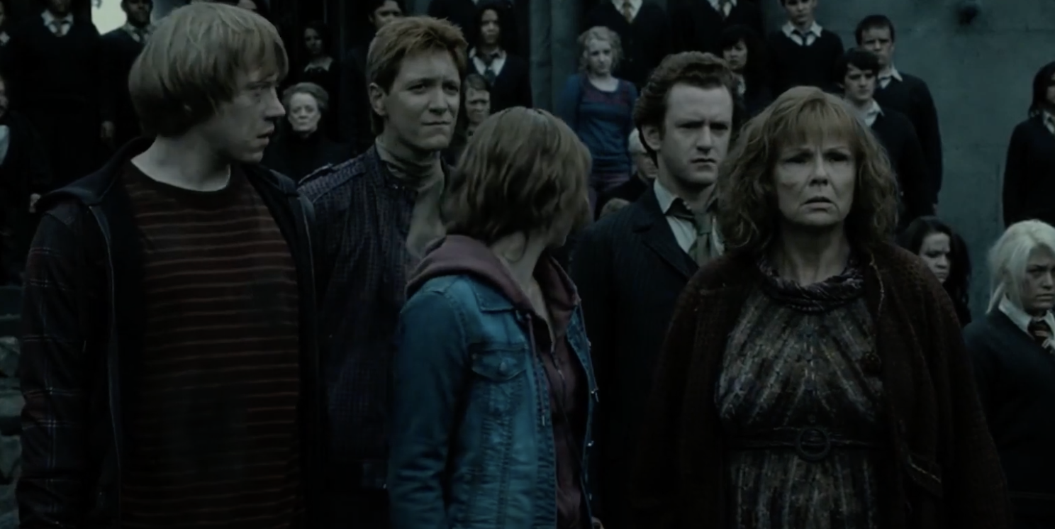 Percy standing with the Weasley family outside of Hogwarts