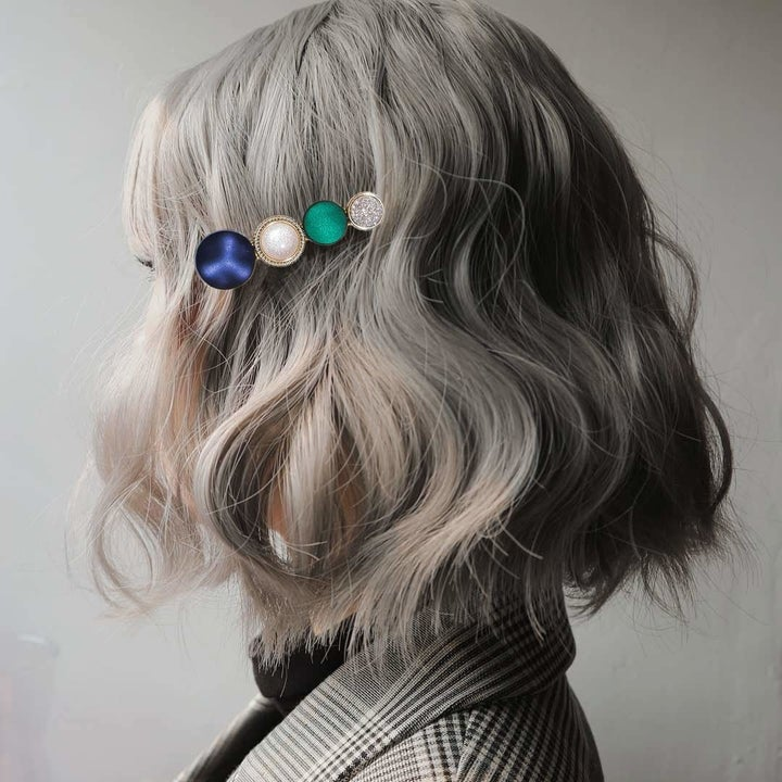 A person wearing one of the hair clips which has green, yellow, and blue jewels