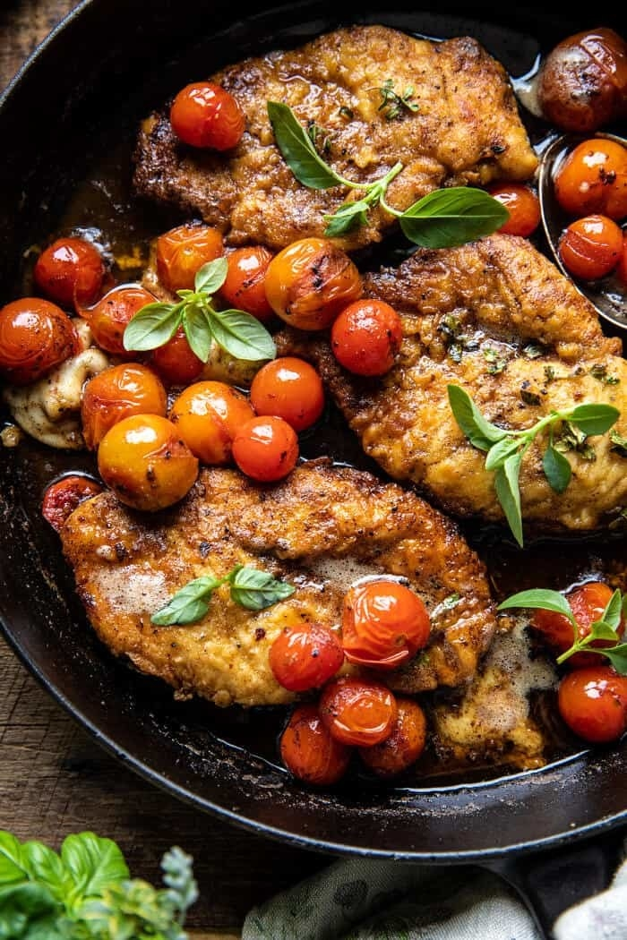 Breaded chicken breasts with burst cherry tomatoes and basil in a skillet.