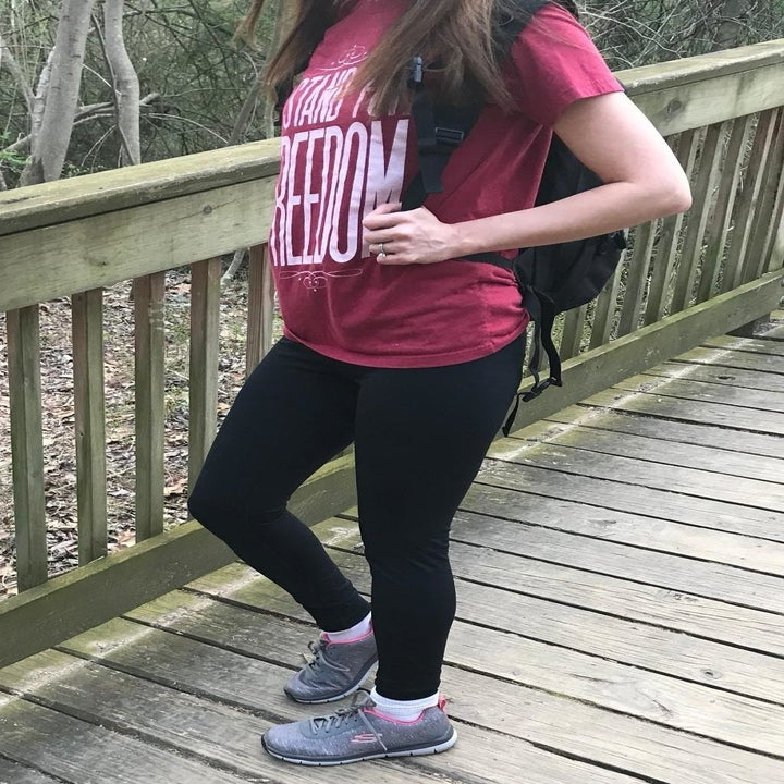 A reviewer wearing the leggings with a T-shirt and sneakers