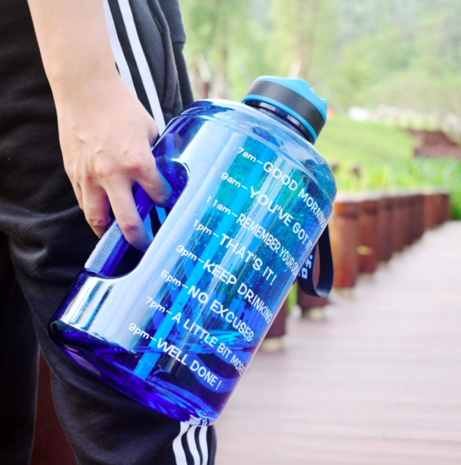 Hand holds blue motivational water bottle with time markers and words of encouragement printed on the side