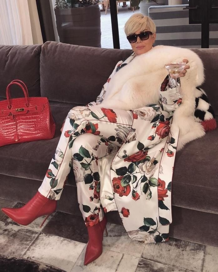 Kris Jenner wearing a luxurious outfit, holding a glass of wine, and posing on a couch