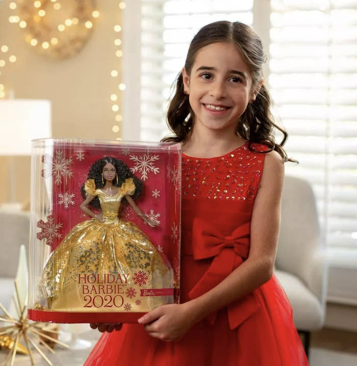 Child holding the Holiday Barbie 2020 box