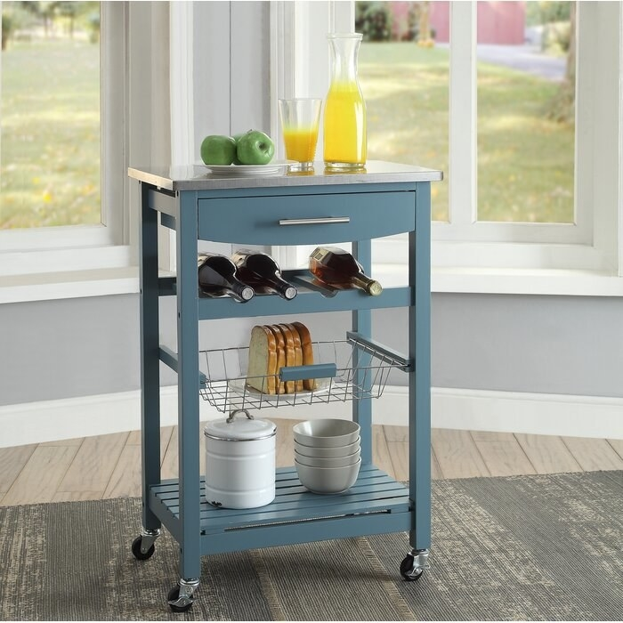 The country blue Winston Porter Kitchen Cart with Stainless Steel Top being used for storage in a kitchen