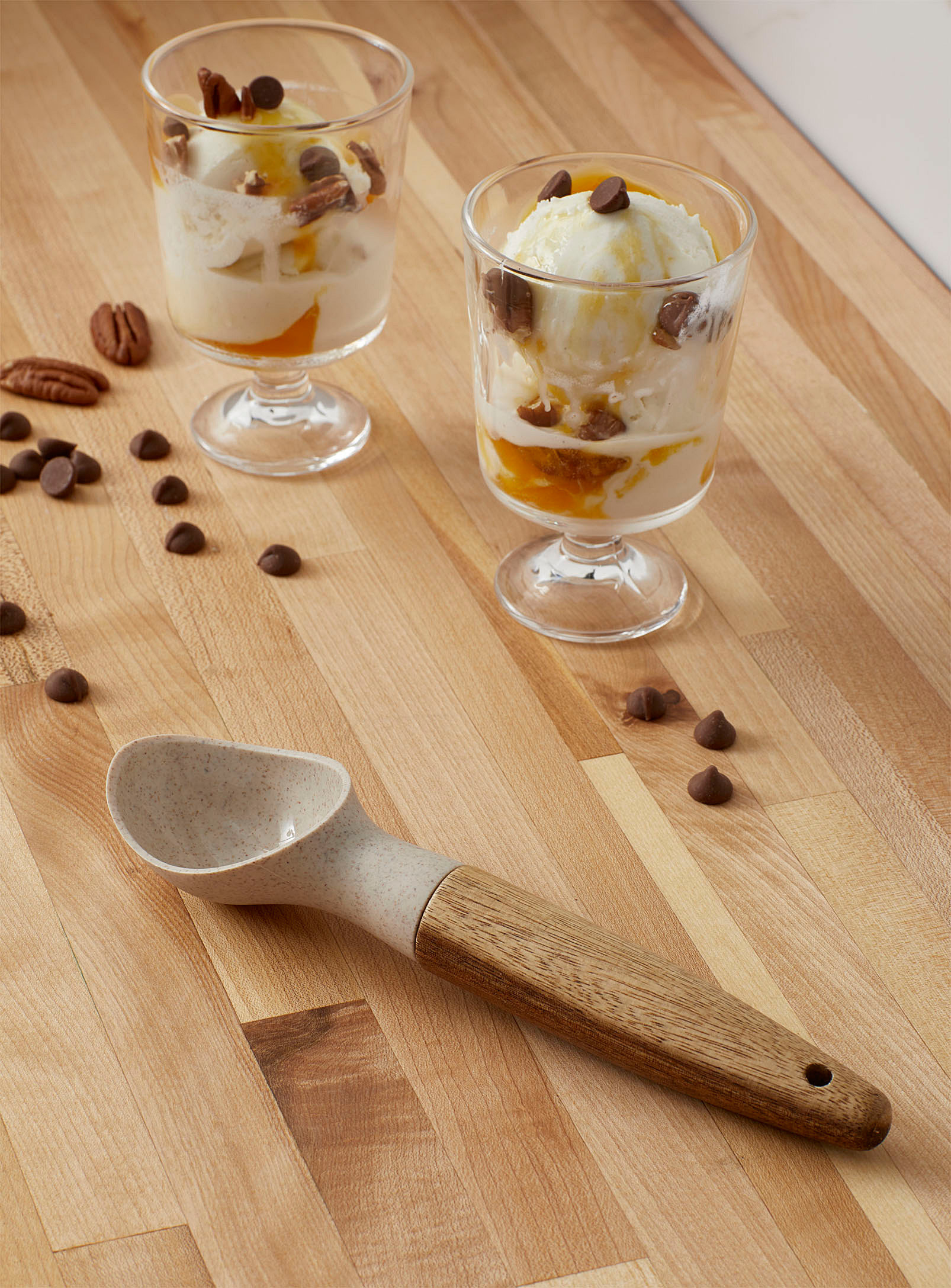 An ice creams scoop beside glass cups filled with ice cream