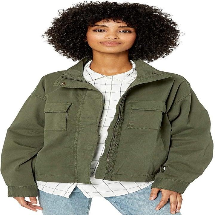 A model wearing a khaki green utility jacket open over a white blouse