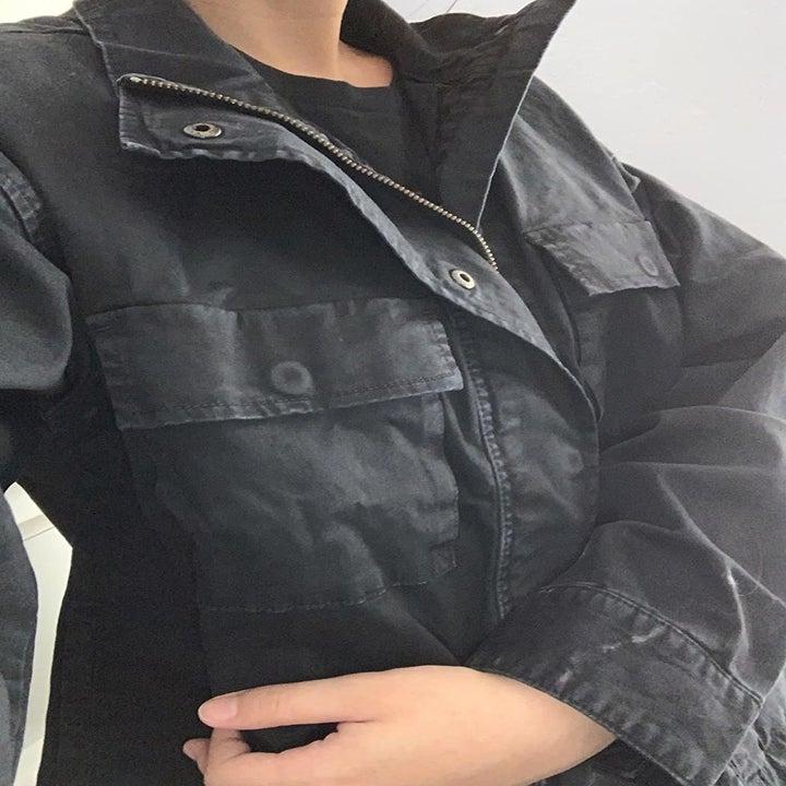 A closeup selfie of a reviewer wearing a black utility jacket zipped up