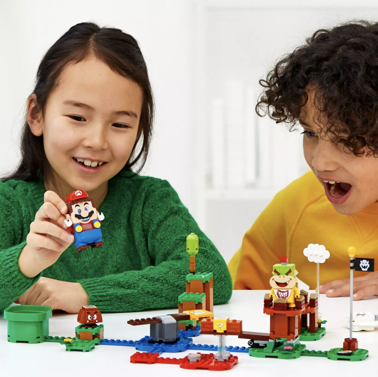 Two children playing with a Super Mario Lego set