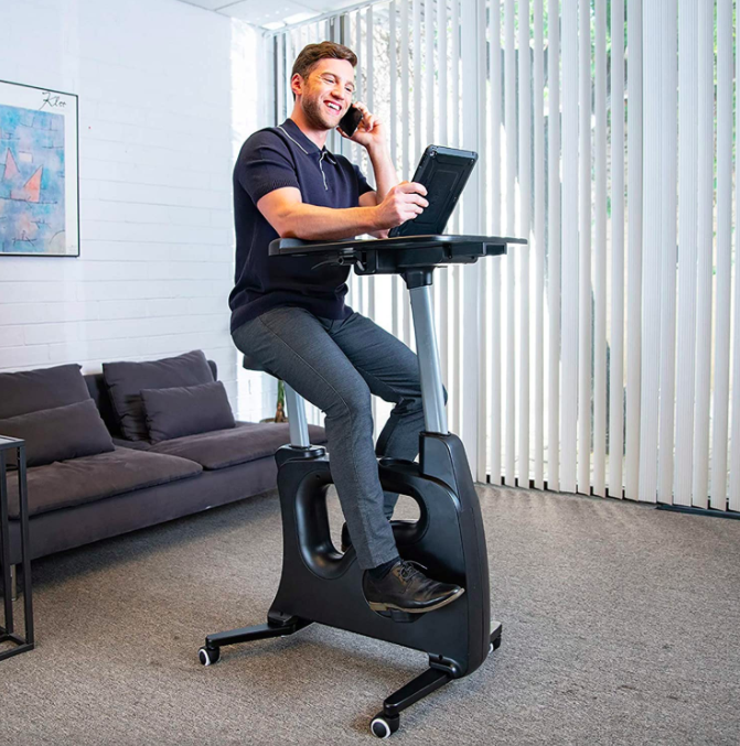 Model sits on black exercise bike with a desk on top