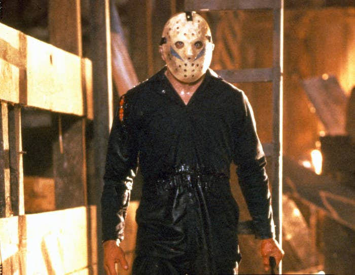 Jason Voorhees in a hockey mask standing in a barn