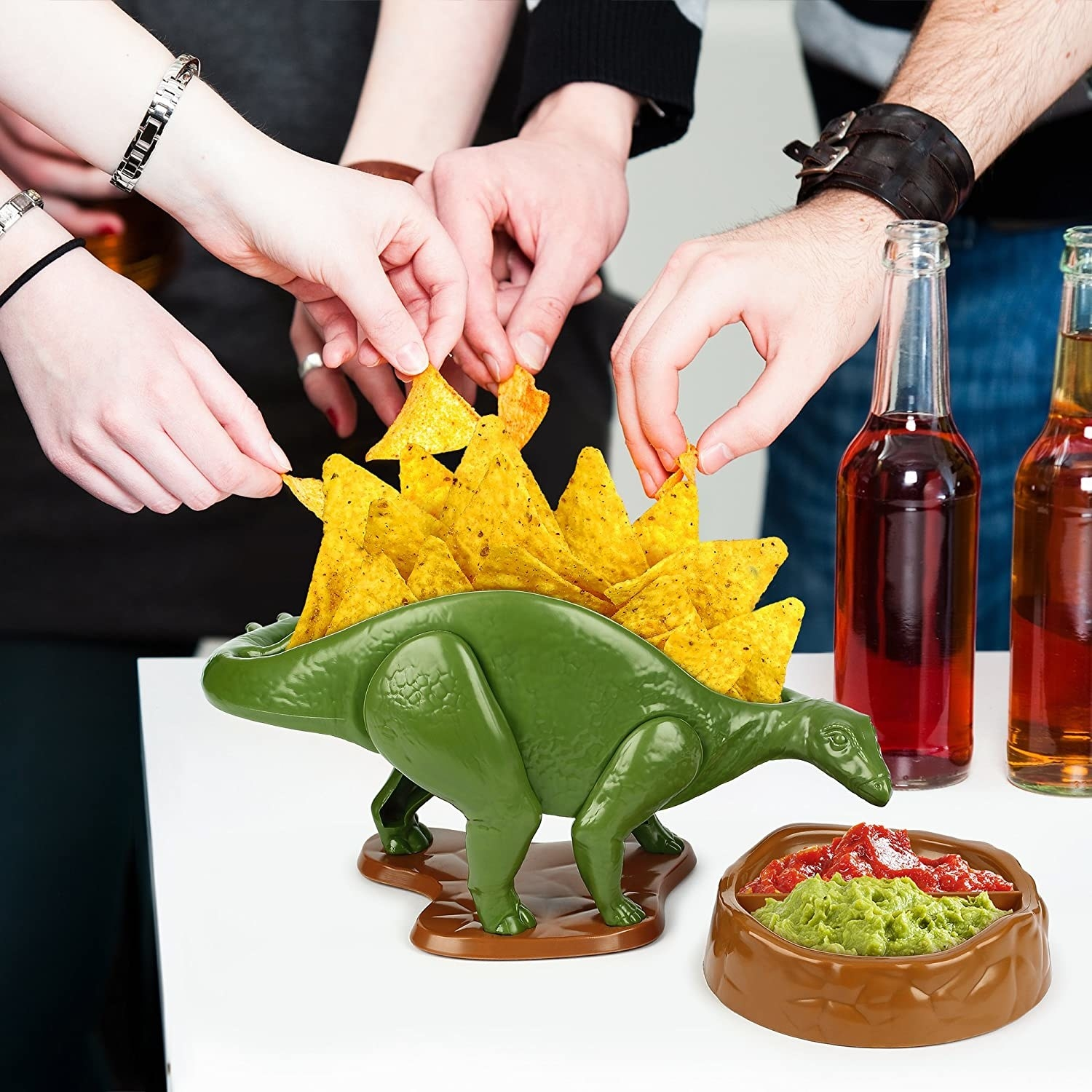 A stegosaurus with chips in its back and a divided bowl with salsa and guacamole