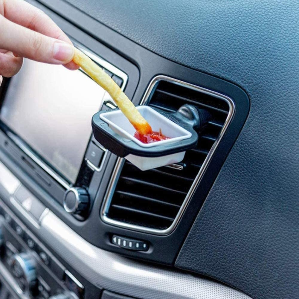 A bottle of dipping sauce attached to a car vent