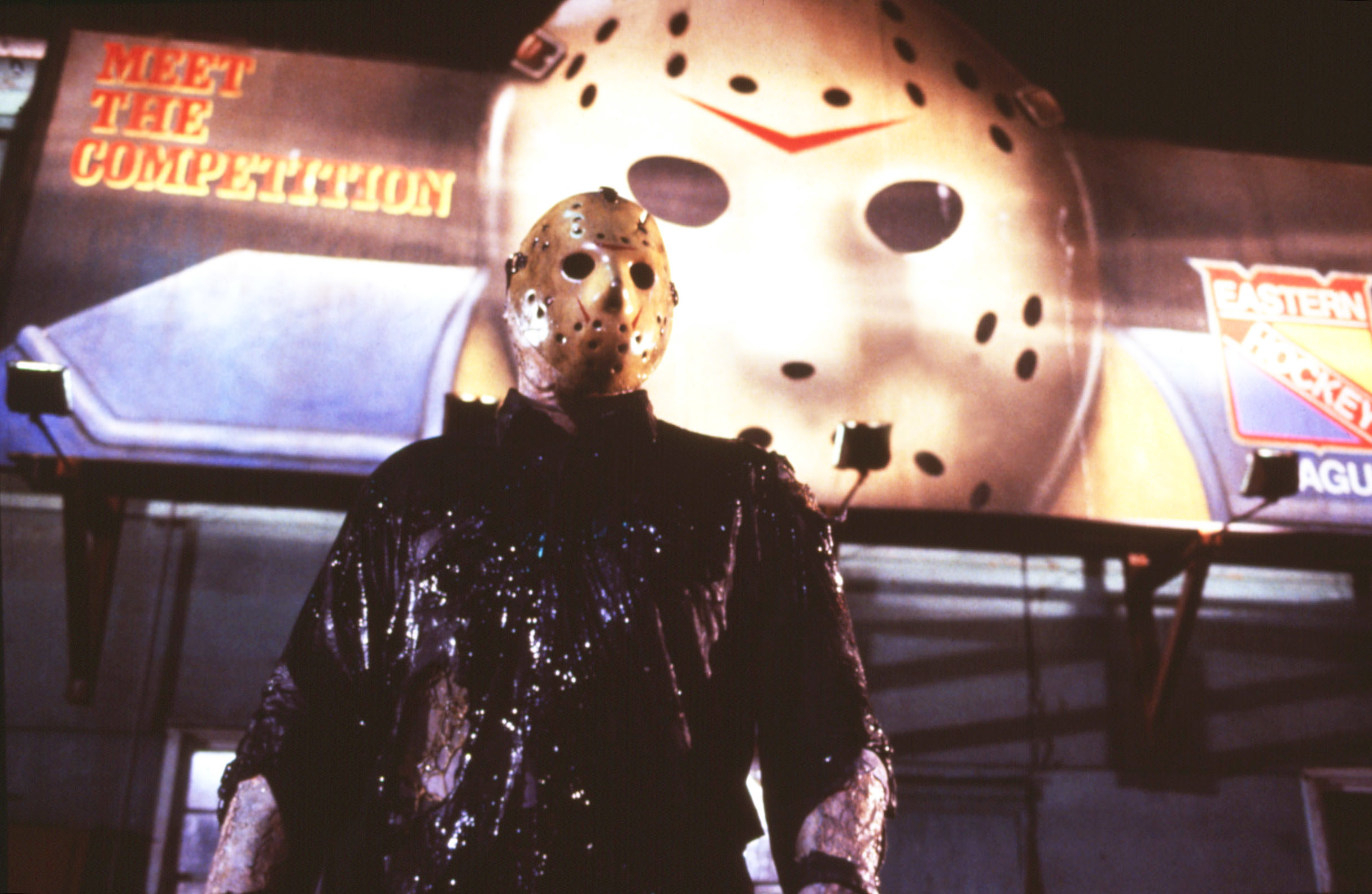 Jason standing in front of a giant billboard with a hockey goalie mask like his on it
