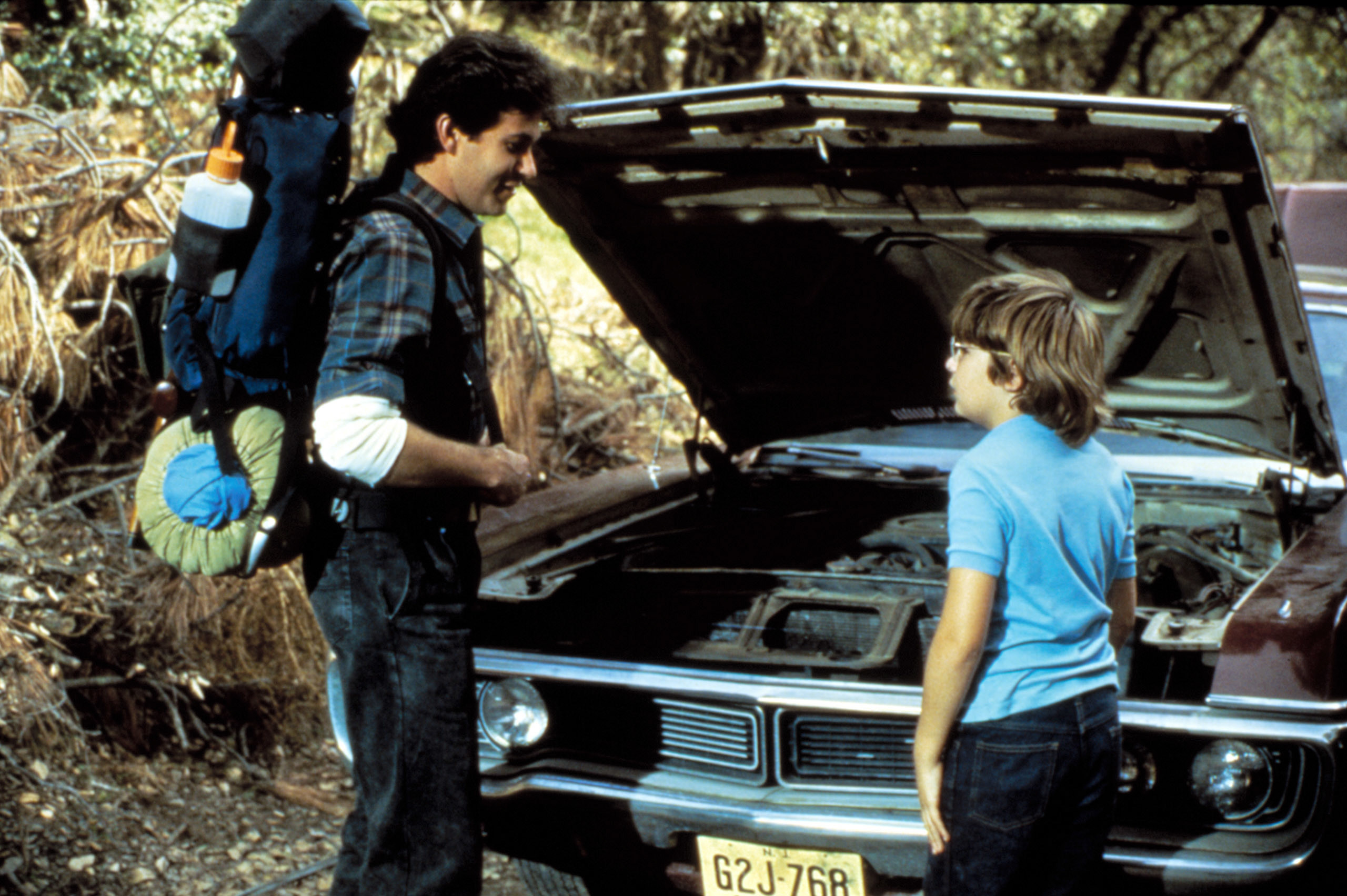 A camper talks to a young boy, Corey Feldman, who's standing in front of a broken down car