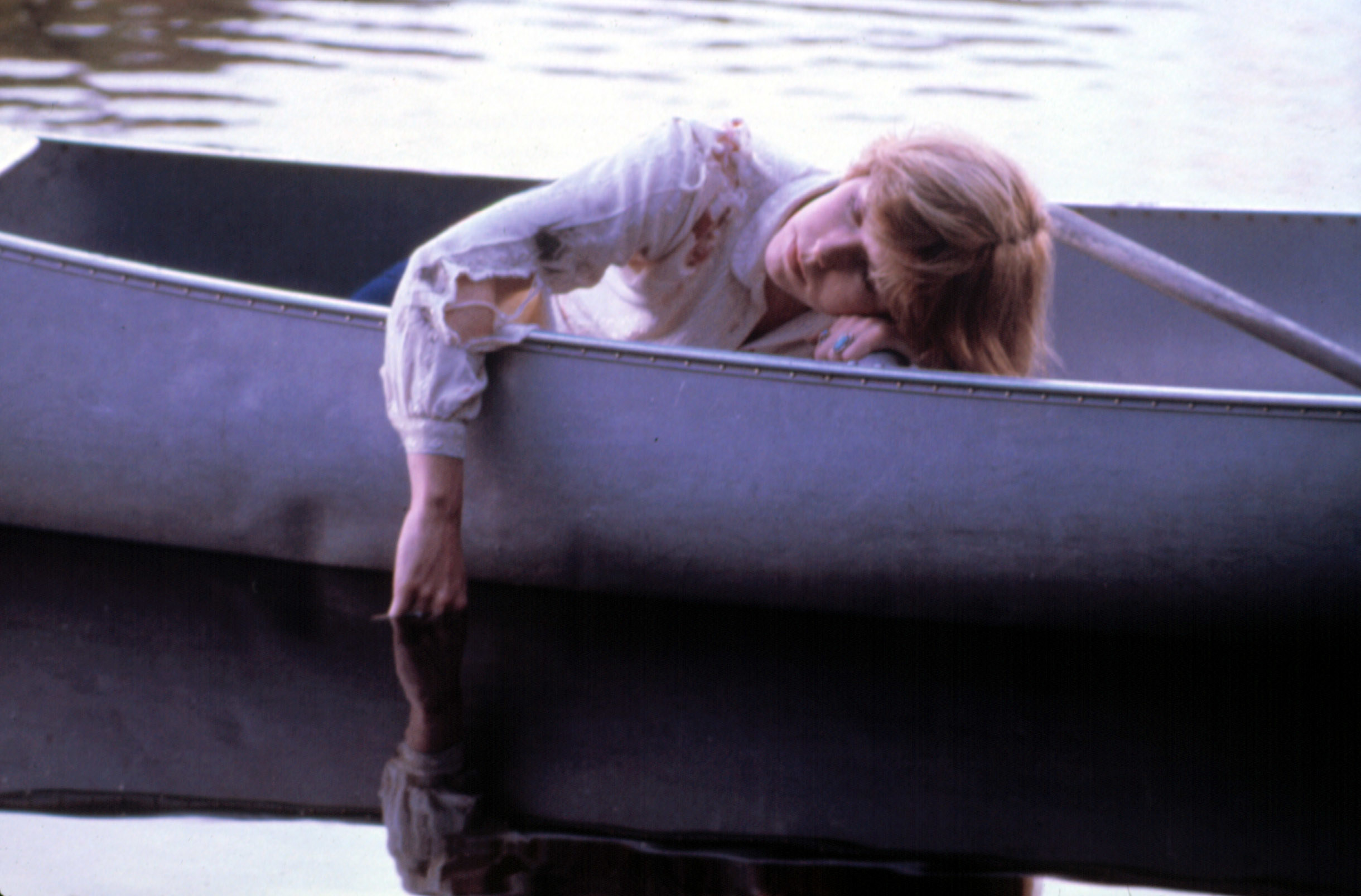 A woman sleeps in a boat with her hand dipped into the lake