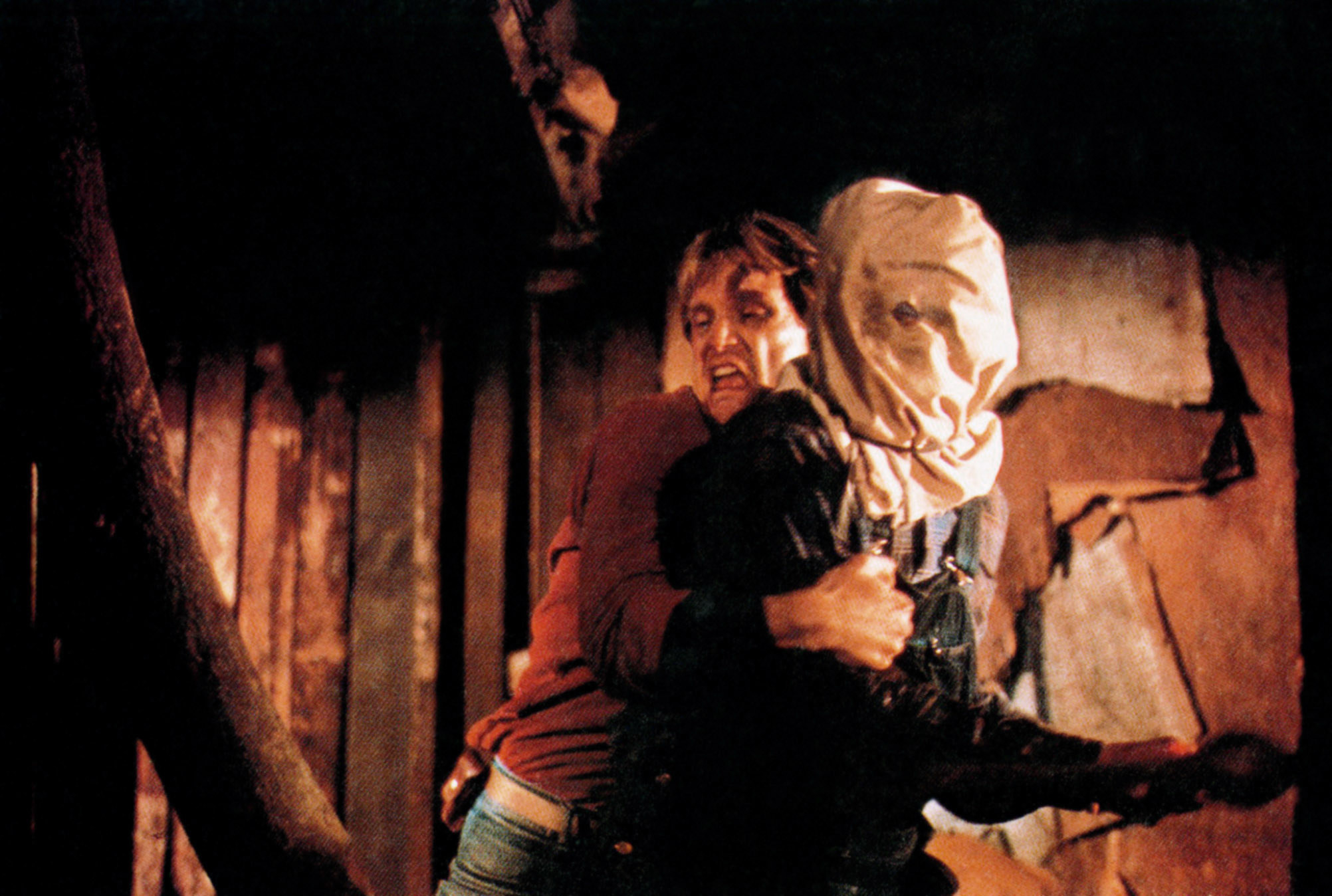 A young man fighting Jason who's wearing a burlap sack over his head